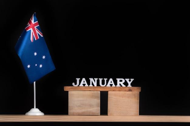 Calendario in legno di gennaio con bandiera australiana su uno spazio nero. vacanze in australia a gennaio.