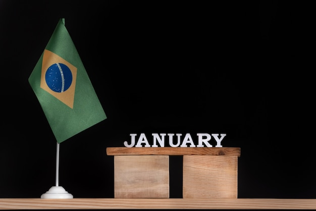 Calendario in legno di gennaio con bandiera brasiliana su uno spazio nero. date del brasile a gennaio.