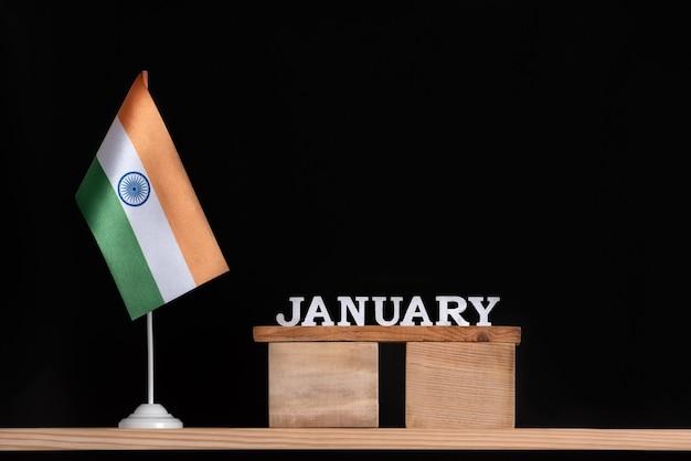 Calendario in legno di gennaio con bandiera indiana su uno spazio nero. vacanze in india a gennaio.