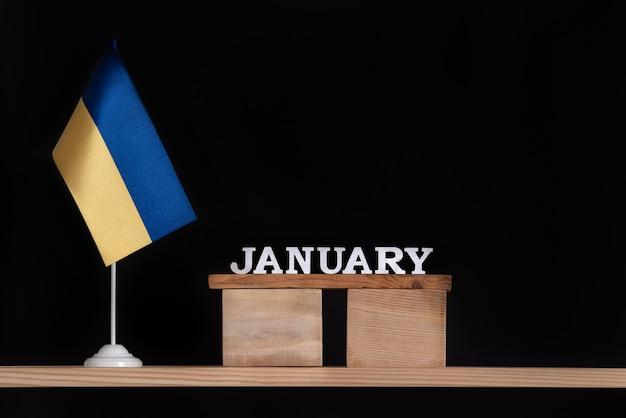 Calendario in legno di gennaio con bandiera ucraina su uno spazio nero. date in ucraina a gennaio.