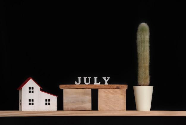 Calendario in legno di luglio, cactus e modello di casa