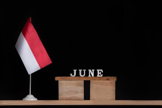 Calendario in legno di giugno con bandiera polacca su superficie nera. vacanze della polonia nel mese di giugno.
