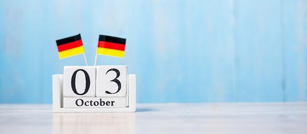 Calendario in legno del 3 ottobre con bandiere della germania in miniatura.