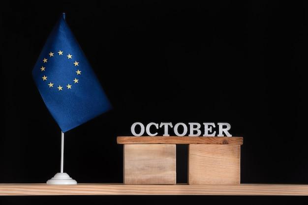 Calendario in legno di ottobre con bandiera ue su superficie nera. unione europea date di ottobre.