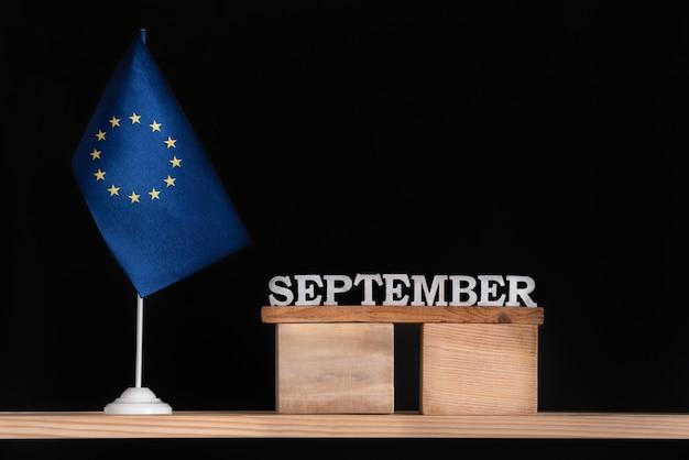 Calendario in legno di settembre con bandiera ue su sfondo nero. unione europea date di settembre.