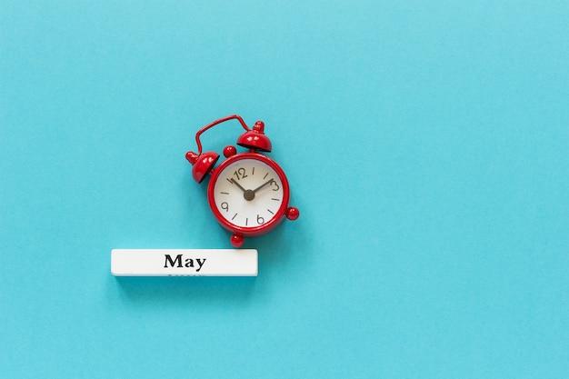 Mese di maggio del calendario di legno del calendario e sveglia rossa sul fondo della carta blu. concetto ciao maggio o arrivederci maggio