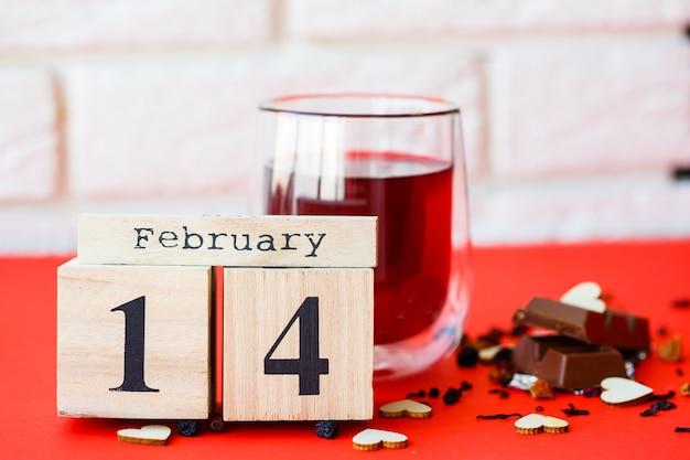 Calendario in legno con la data del 14 febbraio su sfondo rosso brillante. appuntamento romantico. il giorno di san valentino concetto. vista dall'alto, copia dello spazio.