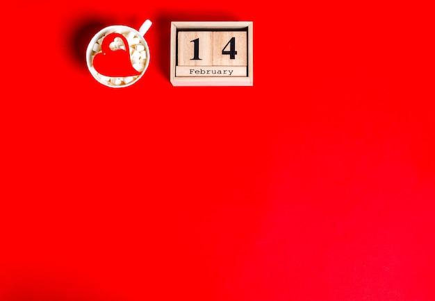 Calendario in legno con la data del 14 febbraio e una tazza bianca con marshmallow e un cuore in rosso