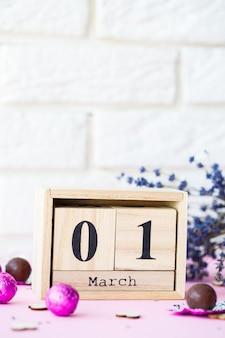 Calendario in legno con la data del 1 marzo su sfondo rosa, un posto per un'iscrizione, il primo giorno di primavera, un ramo secco di lavanda