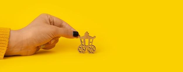 Carrello in legno in mano su sfondo giallo, trasporto vintage, mock-up panoramico