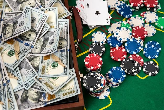 Custodia in legno per fiches da poker con carte da gioco e dollari americani sul tavolo verde. concetto di gioco d'azzardo