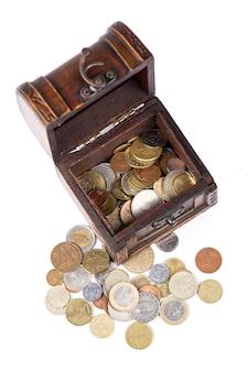 Cofanetto in legno pieno di monete thai isolato su bianco