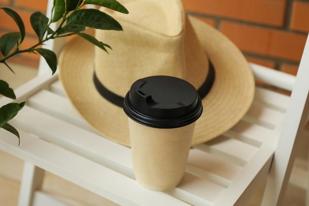 Sedia in legno con cappello, bicchiere di carta e ramo di pianta