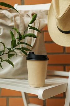 Sedia in legno con cappello, bicchiere di carta e sacchetto di cotone