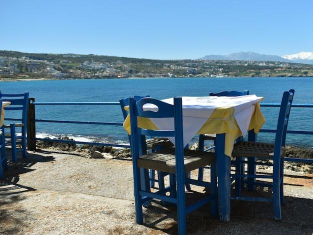 Sedie e tavolo in legno in una taverna sullo sfondo del mare