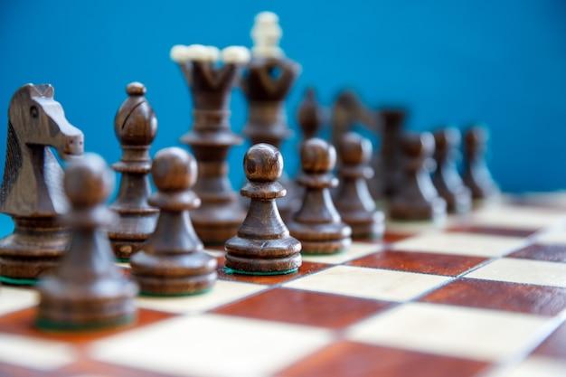 Pezzi degli scacchi in legno sulla scacchiera, lato oscuro prima dell'inizio del gioco
