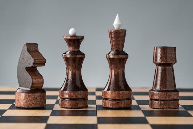 Pezzi degli scacchi in legno su una scacchiera, quattro pezzi neri di fila, concetto, strategia, pianificazione e processo decisionale