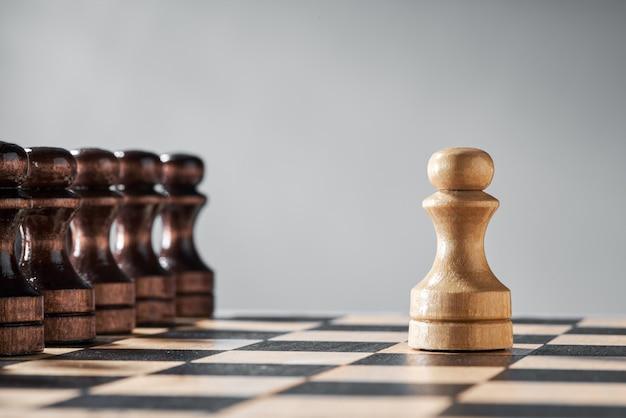 Pezzi degli scacchi in legno su una scacchiera, una pedina bianca contro una serie completa di pezzi neri, il concetto di strategia, pianificazione e processo decisionale