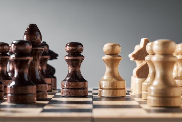 Pezzi degli scacchi in legno su una scacchiera, pedine opposte di diversi colori, il concetto di strategia, pianificazione e processo decisionale