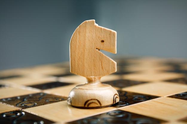 Scacchi in legno, cavallo bianco su scacchiera