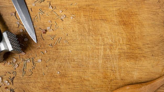 Il tagliere in legno e l'attrezzatura da cucina vista dall'alto per il concetto di cibo