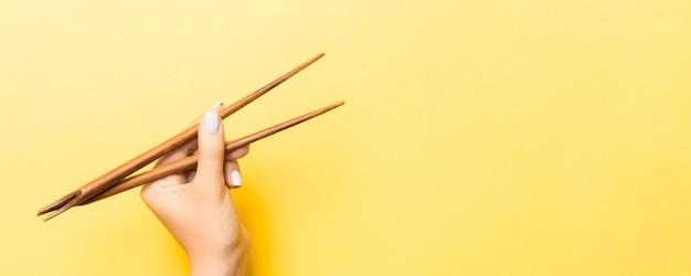 Bacchette di legno in mano femminile su superficie gialla con spazio vuoto per la tua idea