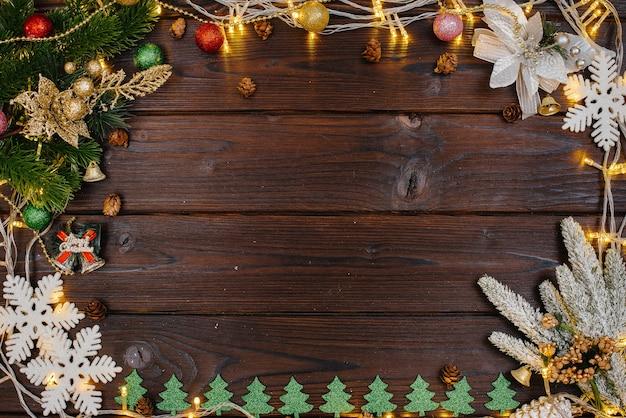 Lo sfondo natalizio in legno è decorato con decorazioni festive, lanterne, fiocchi di neve e rami dell'albero di natale. biglietto natalizio. stagione delle vacanze invernali. felice anno nuovo.
