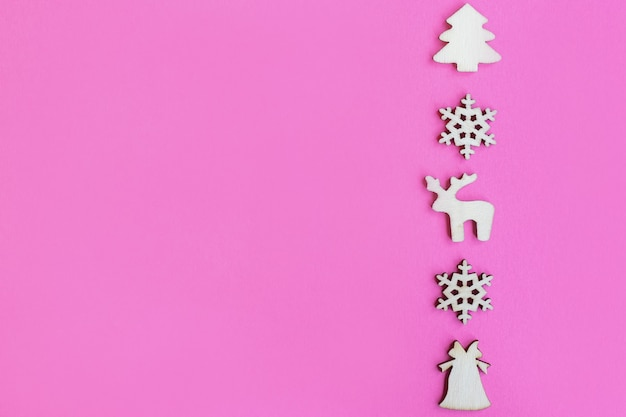 Giocattoli di natale in legno su sfondo rosa, vista dall'alto, piatto laico, concetto minimo di nuovo anno, per il design o una cartolina