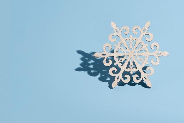 Decorazione per albero di natale in legno a forma di fiocco di neve su sfondo blu con spazio di copia: concetto minimo di capodanno