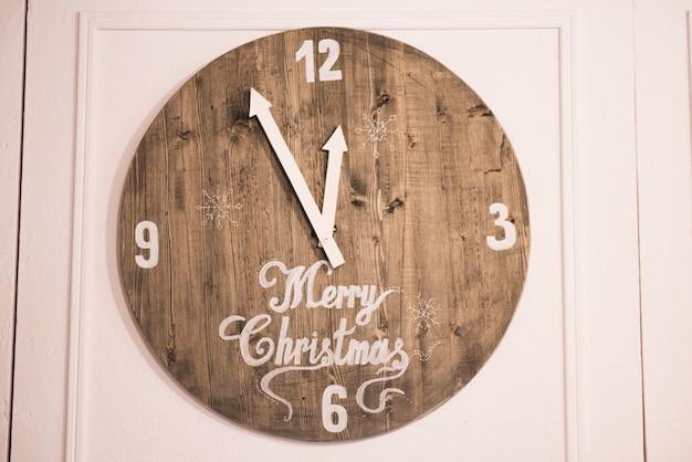 Orologio di legno su uno sfondo bianco con la scritta buon natale, le lancette battono la mezzanotte