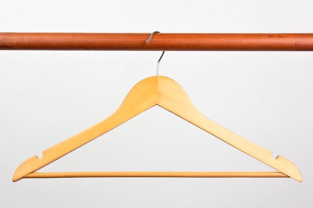 Appendiabiti in legno su un bianco. la scelta dello stile di vestiti alla moda