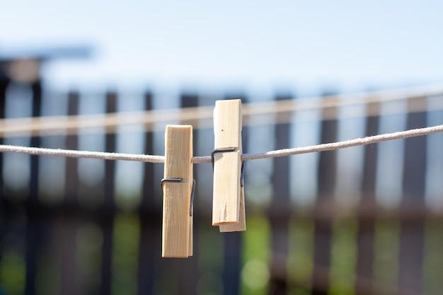 Mollette di legno su una corda da bucato sullo sfondo di una staccionata in legno.