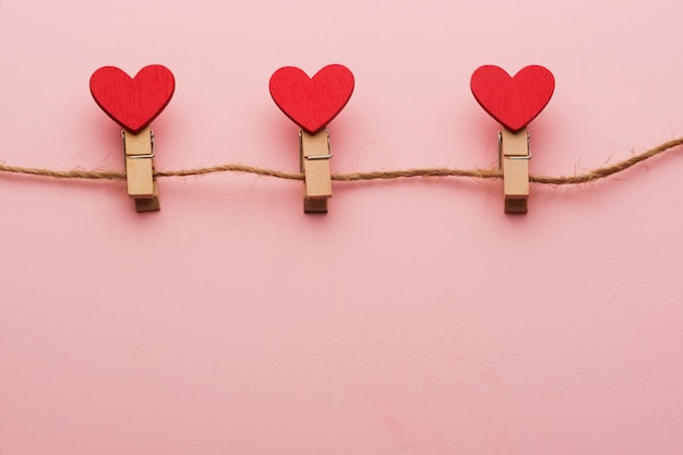 Mollette di legno con cuori su una corda su uno sfondo rosso