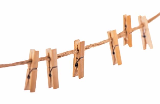 Mollette in legno con la corda su una superficie bianca Foto Premium