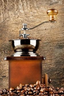 Macinacaffè in legno con chicchi di caffè tostato