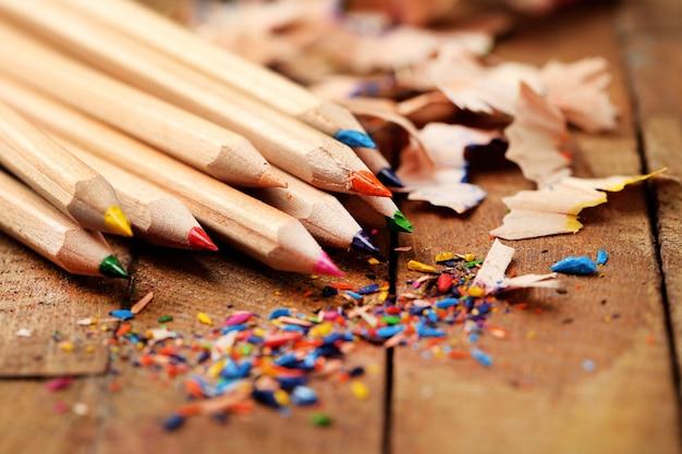 Matite colorate in legno con trucioli di affilatura, su tavola di legno