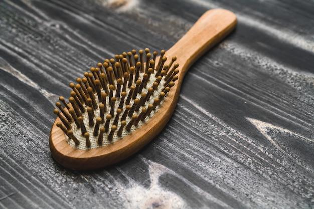 Il pettine di legno giace sul tavolo, spazzola per capelli problematici