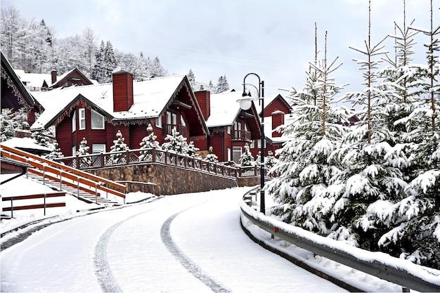 Case di legno casa per le vacanze in località di villeggiatura di montagna ricoperta di neve fresca in inverno. bella strada invernale dopo la nevicata.
