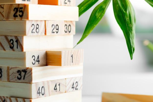 Costruttore creativo in legno da blocchi con numeri contro la parete leggera. gioco per guadagnare, sviluppare e educare.