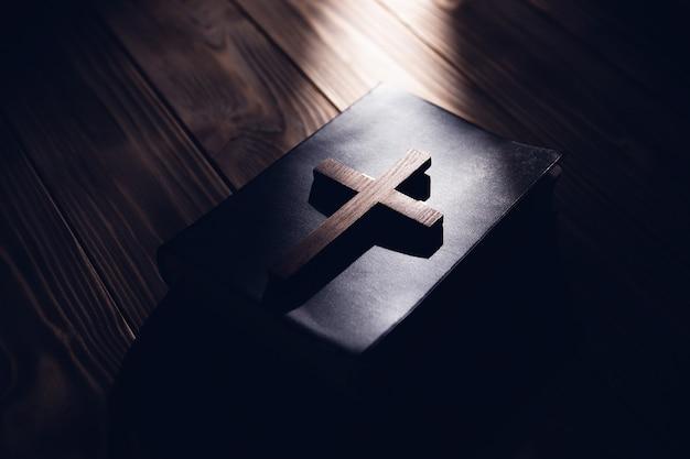 Croce di legno sulla sacra bibbia su sfondo di legno
