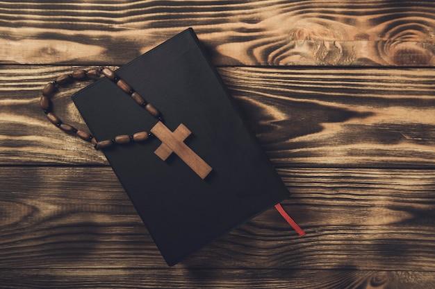 Croce di legno sulla sacra bibbia sulla tavola di legno