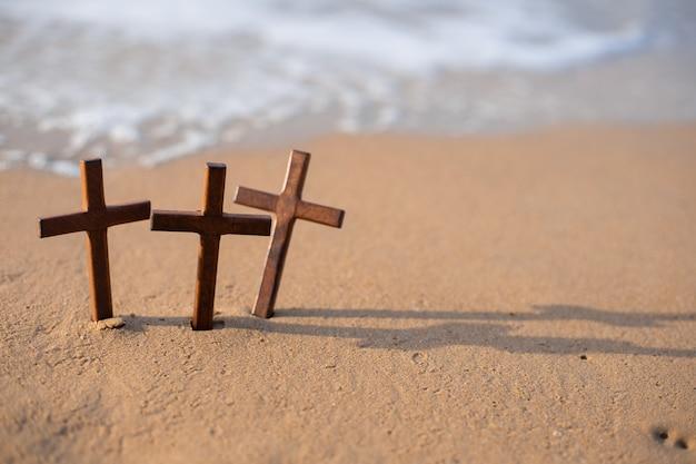 Una croce di legno sulla sabbia sulla spiaggia.