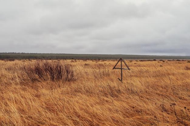 Croce di legno nella steppa. vecchio villaggio russo di pomerania.