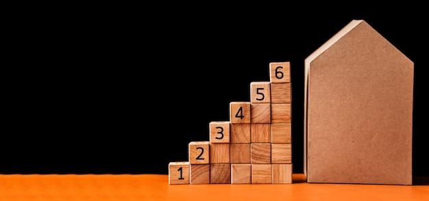 Cubo di legno con casa di modello di carta cartone