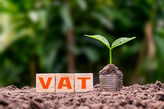 Blocchi cubo di legno etichettati iva con alberi che crescono su pile di monete. il concetto di adeguamento dell'aliquota dell'imposta sul valore aggiunto (iva) dei prodotti agricoli.