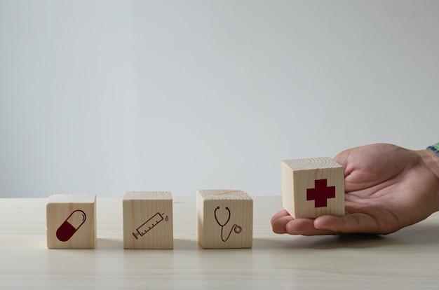Cubo di legno sanitario e icona medica sul tavolo. concetto di assistenza sanitaria e assicurazione.