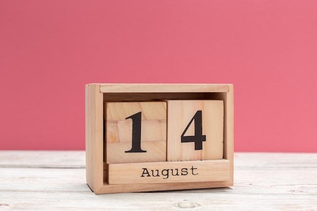 Calendario a forma di cubo di legno per il 14 agosto sul tavolo di legno