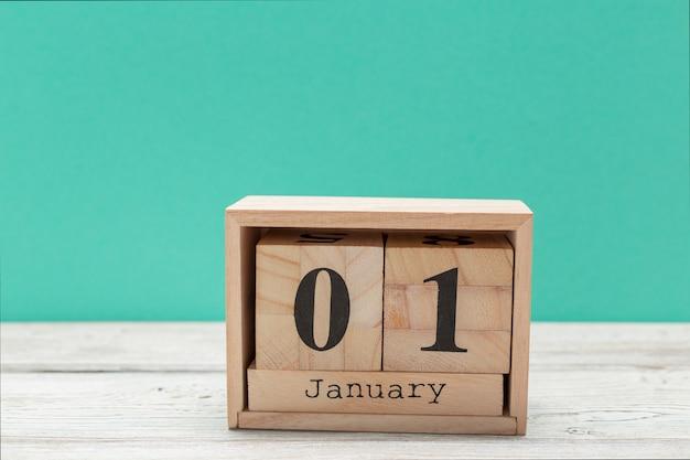 Calendario in legno a forma di cubo per il 1 gennaio sul tavolo di legno