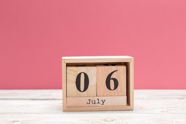 Calendario in legno a forma di cubo per il 6 luglio sul tavolo di legno