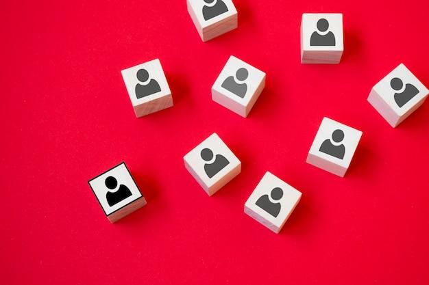 Il cubo di legno con l'icona della persona si distingue dalla massa su sfondo rosso. opinione dissenziente, punti di vista divergenti e concetti diversi